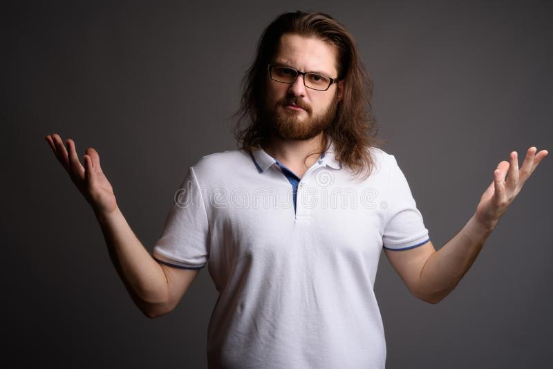 Young bearded man wearing white polo shirt against gray backgrou. Studio shot of young bearded man wearing white polo shirt against gray background royalty free stock photos