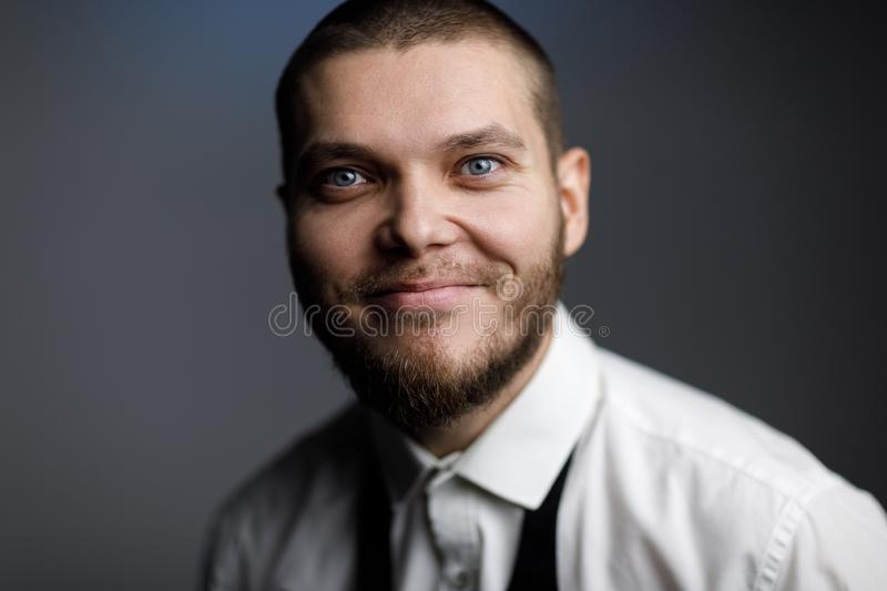 Young bearded man in a white shirt and bow tie. Portrait of happy bearded man in white shirt and untied bow tie royalty free stock photos