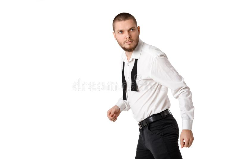 Young bearded man in a white shirt and bow tie. Portrait of young bearded man in white shirt and untied bow tie royalty free stock photography