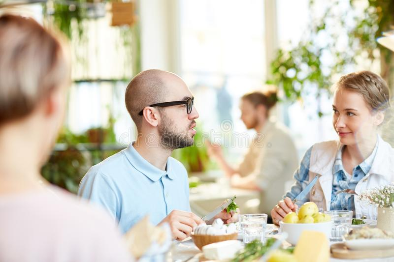 Male talking with woman and cutting salad royalty free stock photo