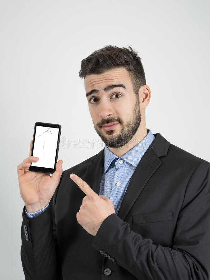 Young bearded sad businessman pointing finger at broken smartphone screen royalty free stock photography