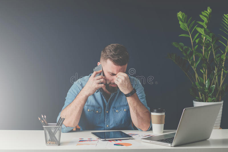 Young bearded sad businessman is sitting at table, covering his face with his hand and talking on cell phone. stock image