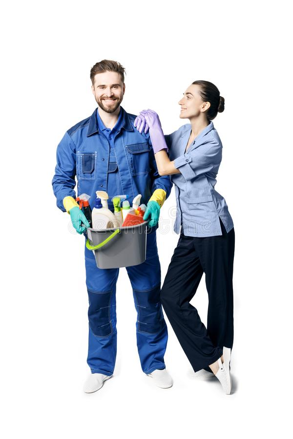 A young bearded smiling man in the uniform of a janitor holds a basket with moisturizing products, and maid-shaped women stock image
