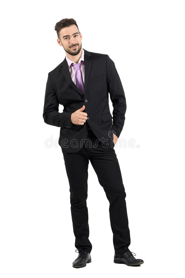 Young bearded successful man in suit with thumbs up smiling at camera. Full body length portrait isolated over white studio background royalty free stock image
