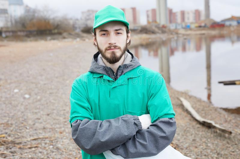 Volunteer with arms crossed. Young bearded volunteer in green uniform standing with arms crossed and looking at camera on shore royalty free stock photo