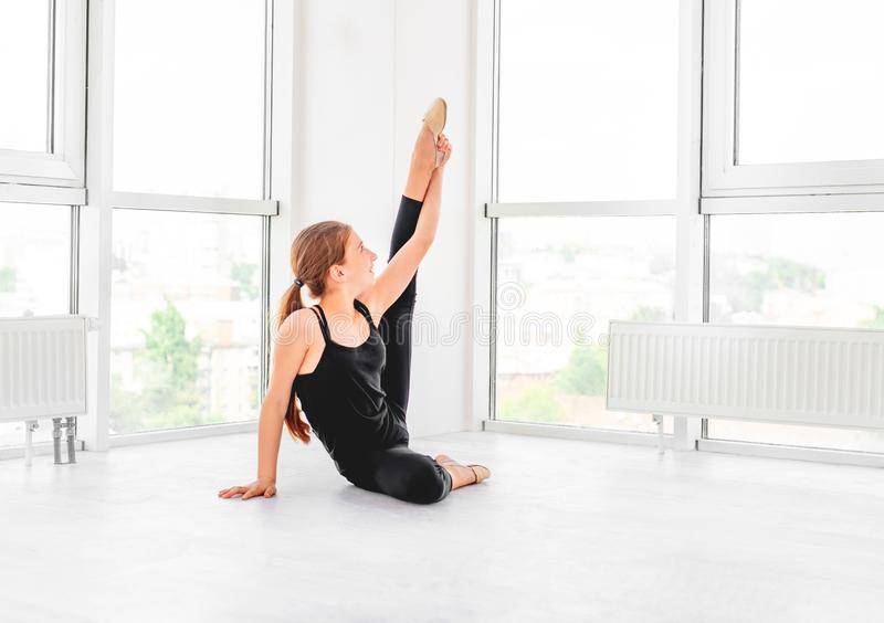 Young girl showing flexibility. Young beatiful dancer is showing her flexibility in white dancing room stock photos
