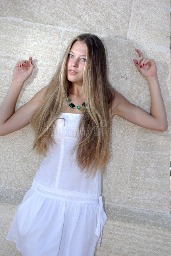 Young beaty in white over wall. Young beaty in white over beige wall stock image