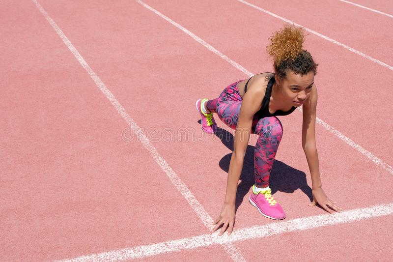 A young beautiful African American girl in a sporty black T-shirt and pink sneakers is preparing to race on the starting strip of royalty free stock photos