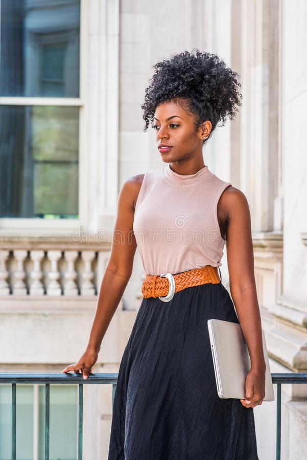 Young beautiful African American woman with afro hairstyle wearing sleeveless light color top, belt, black skirt, holding laptop. Computer, standing in vintage stock image