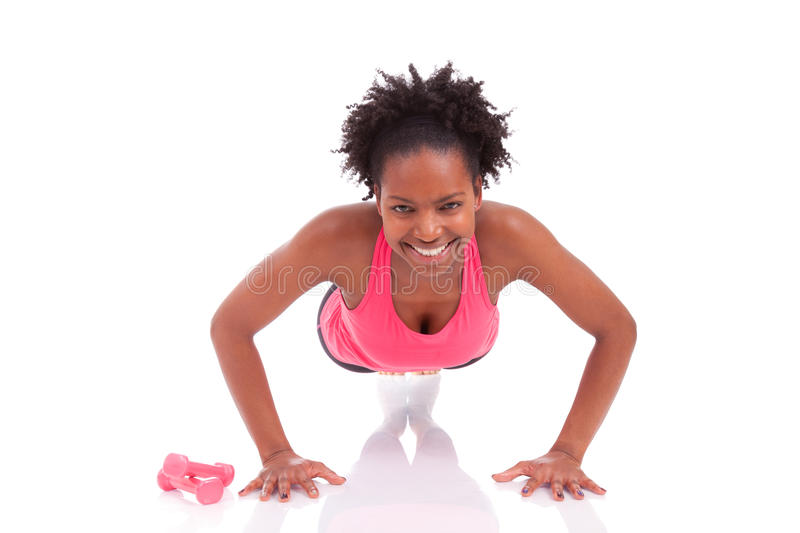Young beautiful african fitness woman doing push up exercises on. Floor,isolated on white background royalty free stock photography