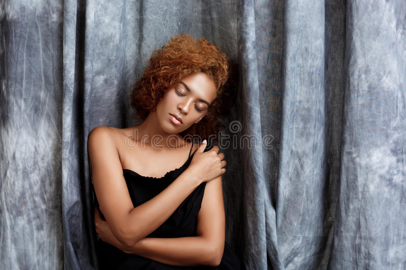 Young beautiful african girl posing, wrapping up in grey cloth. royalty free stock photography