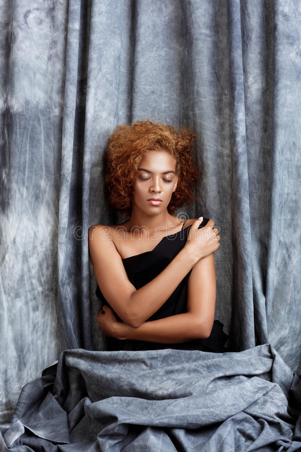 Young beautiful african girl posing, wrapping up in grey cloth. stock photo