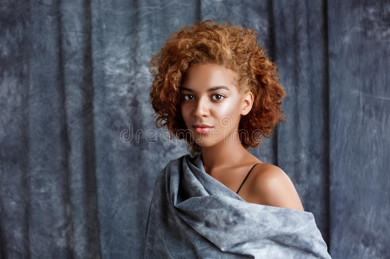 Young beautiful african girl posing, wrapping up in grey cloth. Young beautiful african girl looking at camera, posing, wrapping up in grey cloth. Copy space stock photos