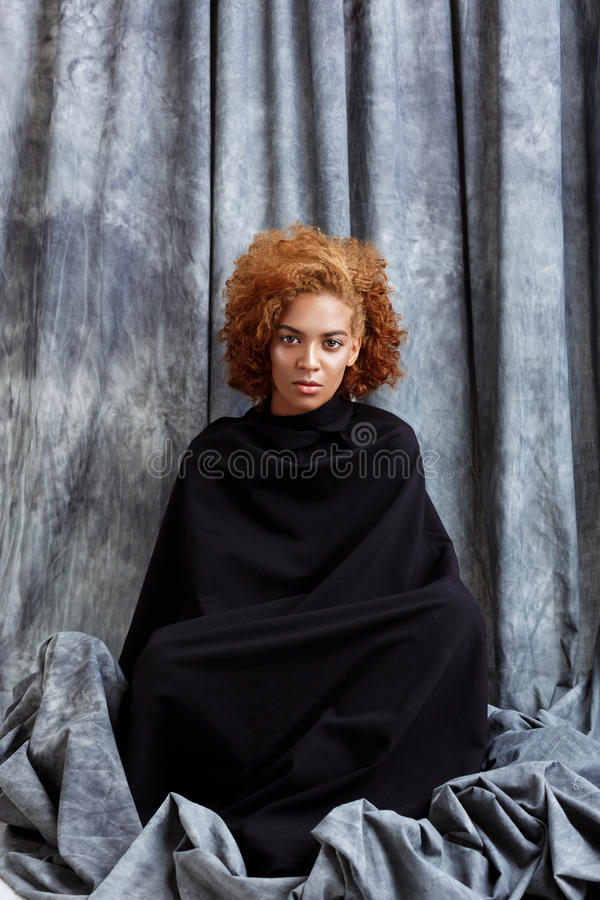 Young beautiful african girl posing, wrapping up in grey cloth. royalty free stock photos