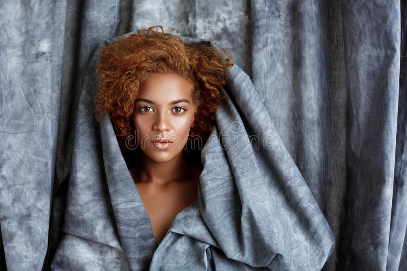 Young beautiful african girl posing, wrapping up in grey cloth. stock photography