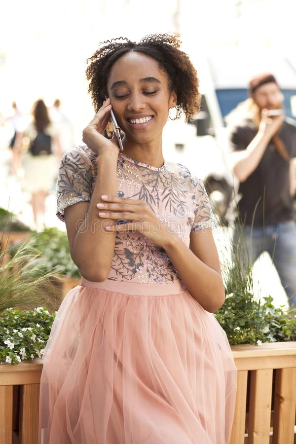 Young beautiful African girl talking on cell phone outdoors in pink dress stock photography