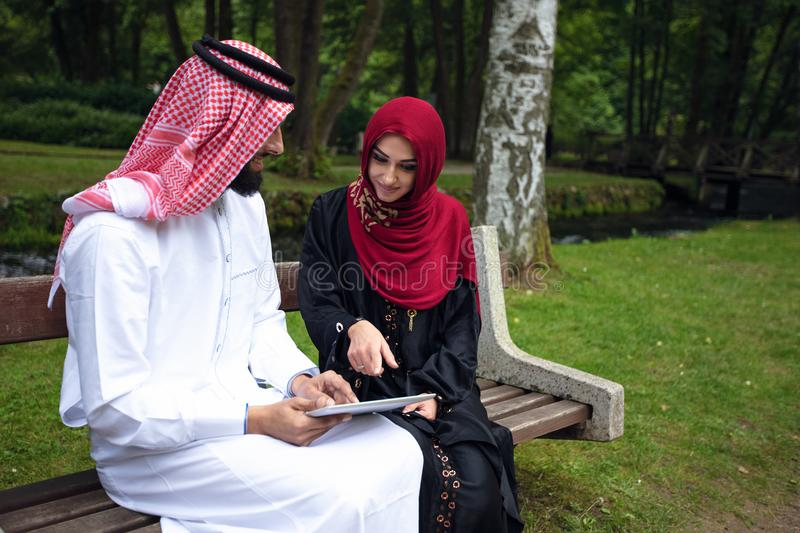 Young beautiful Arabian couple casual and hijab, Abaya, taking a selfie on the lawn in summer park. royalty free stock image