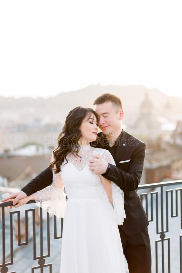Young beautiful Asian bride and groom, happy couple at sunset in old European city. Wedding love story in Europe. royalty free stock photography
