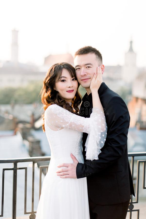 Young beautiful Asian bride and groom, happy couple at sunset in old European city. Wedding love story in Europe. stock image