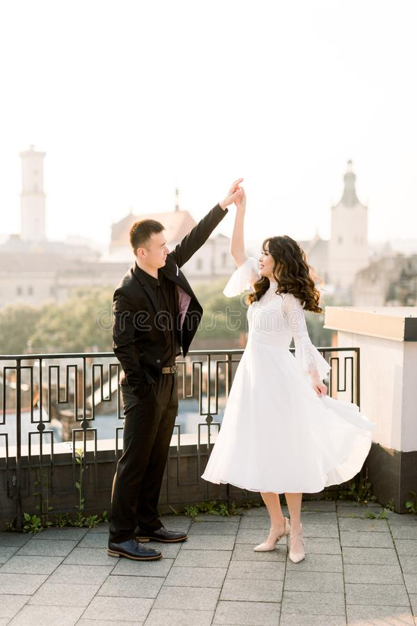 Young beautiful Asian bride and groom on the wedding day walking and dancing on the rooftop of old city. Ancient city stock images