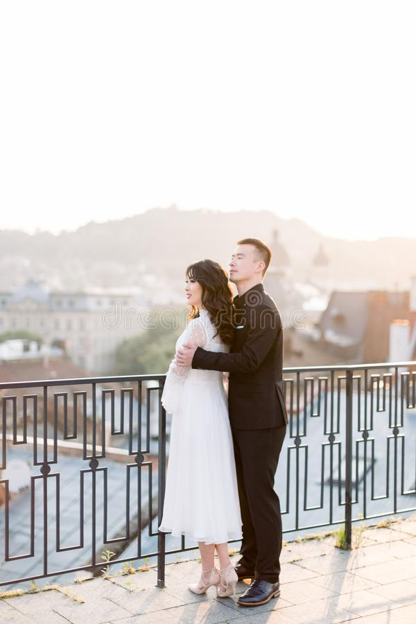 Young beautiful Asian bride and groom on the wedding walk, standing on the terrace of building, man embracing woman from stock photography