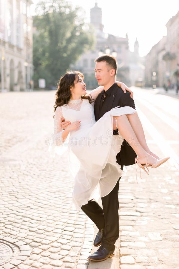 Young beautiful Asian bride and groom on the wedding walk through the streets of old European city. Man holding woman on royalty free stock images