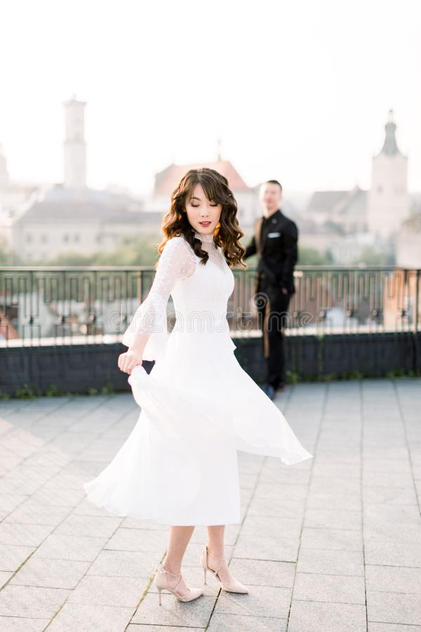 Young beautiful Asian bride in white wedding dress dancing on the terrace of ancient city. Groom standing on the stock photo