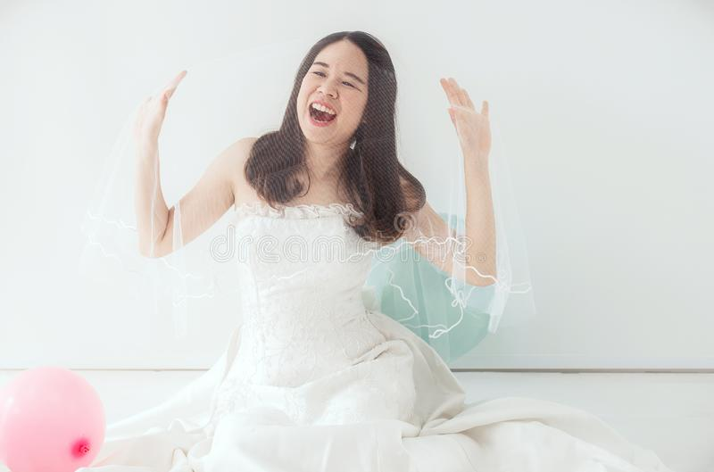 Young beautiful asian bride woman in white dress feeling Happy and funny with balloon stock photography