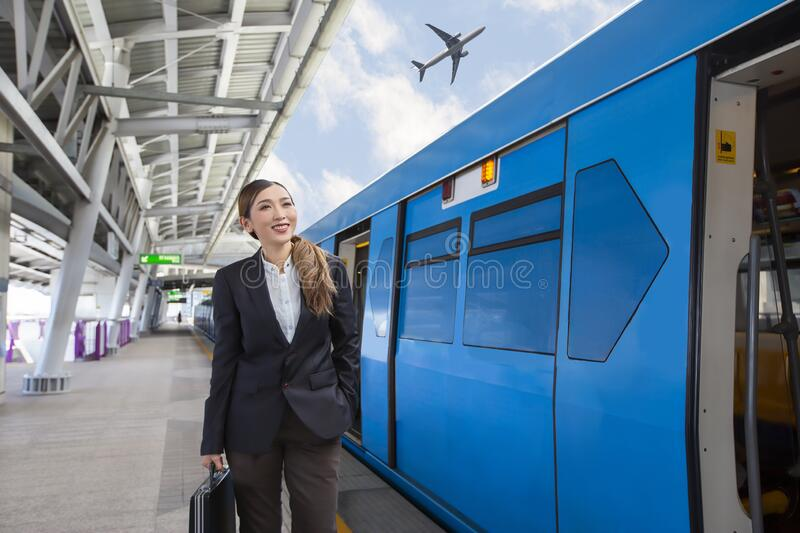 Young beautiful Asian businesswoman holding a bag and waiting for the train to arrive at airport rail link skytrain station stock image