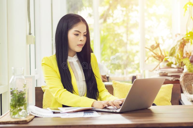 Young beautiful Asian businesswoman sitting at table in coffee shop working with laptop.  royalty free stock photo