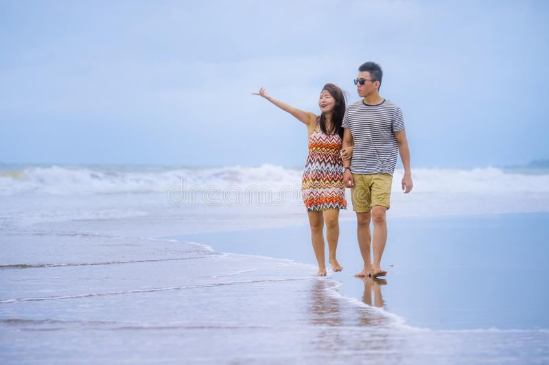 Young beautiful Asian Chinese couple walkingyoung beautiful Asian Chinese couple walking together holding hands on the beach. Young beautiful Asian Chinese royalty free stock photography