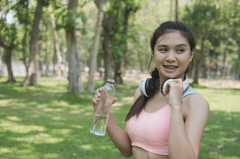 young beautiful asian fitness athlete woman holding drinking water after work out exercising at summer green park. royalty free stock photo