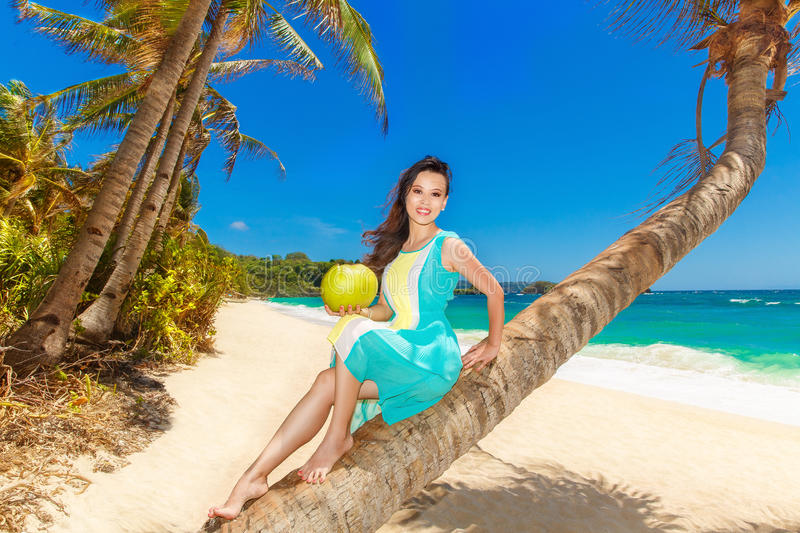 Young beautiful Asian girl with coconut on the palm tree on a t. Ropical beach. Tropical sea in the background. Summer vacation concept royalty free stock photography
