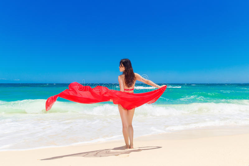 Young beautiful Asian girl with red cloth on the beach of a tropical island. Summer vacation concept. stock image