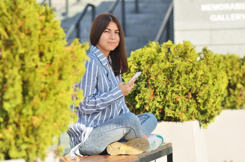 Young beautiful is asian girl sitts on the bench near green tress and listen to music. Spring sunny day stock photo