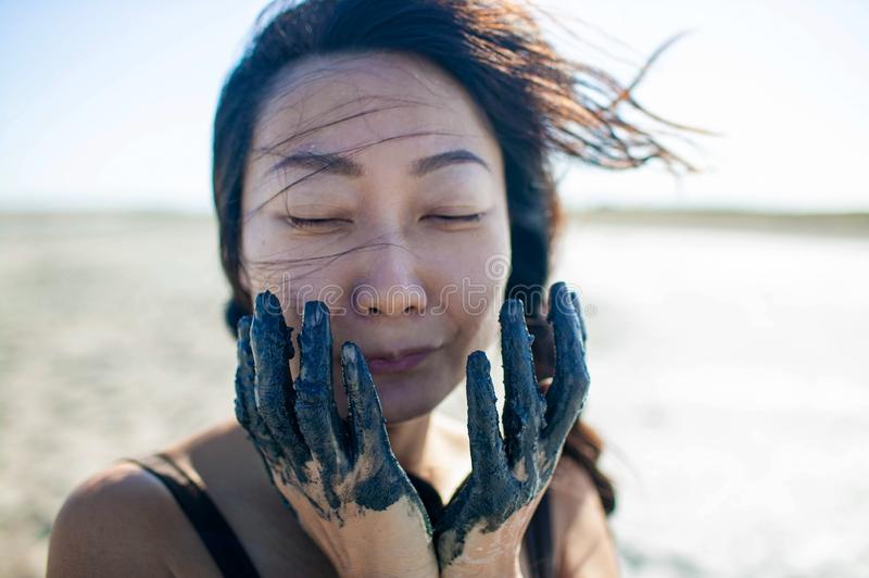 Young beautiful asian woman applying a black cosmetic mask for the face of the therapeutic black mud. Spa treatment and face beaut. Y concept. Female face care stock photography