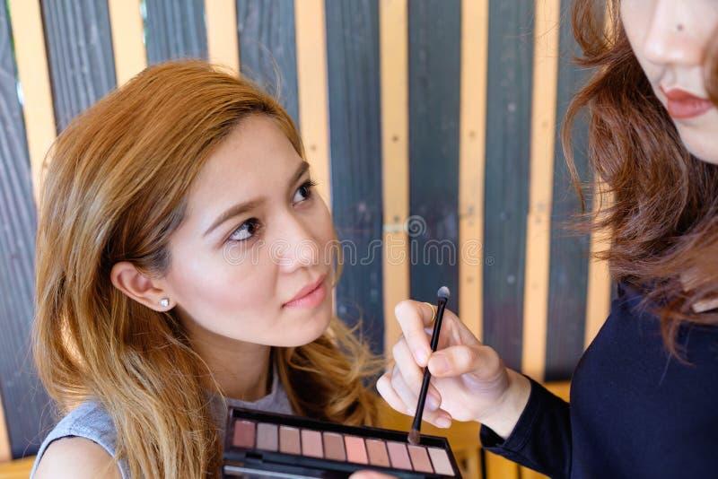 Young beautiful asian woman applying make-up stock photo