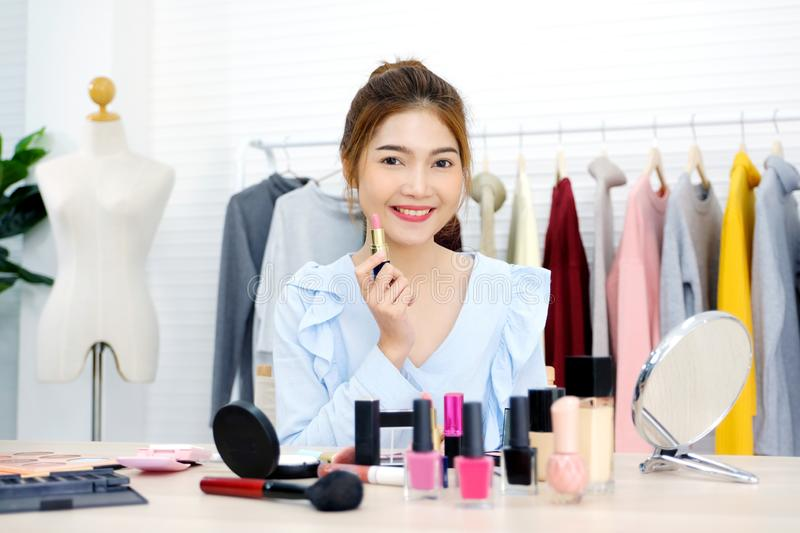 Young beautiful asian woman beauty blogger applying makeup smiling and look at camera, portrait of asian attractive female holding stock images