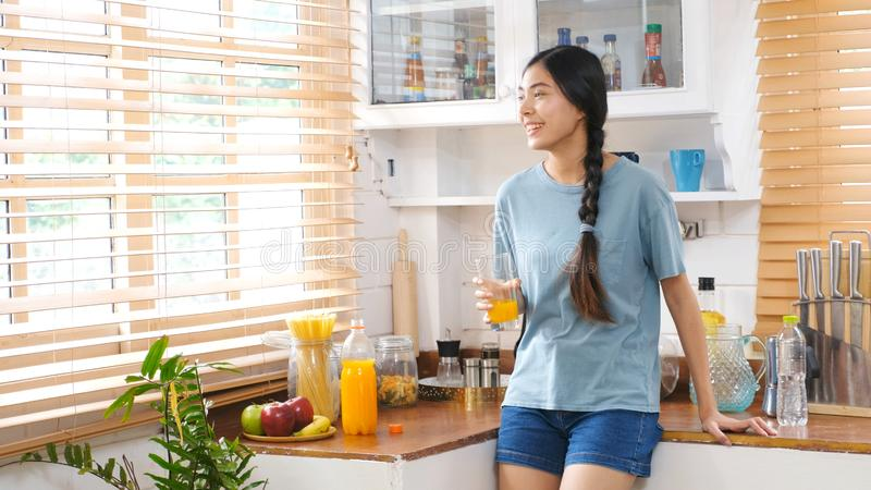 Young beautiful asian woman drinking orange juice and smiling while standing by window in kitchen background, peolpe and healthy royalty free stock photography