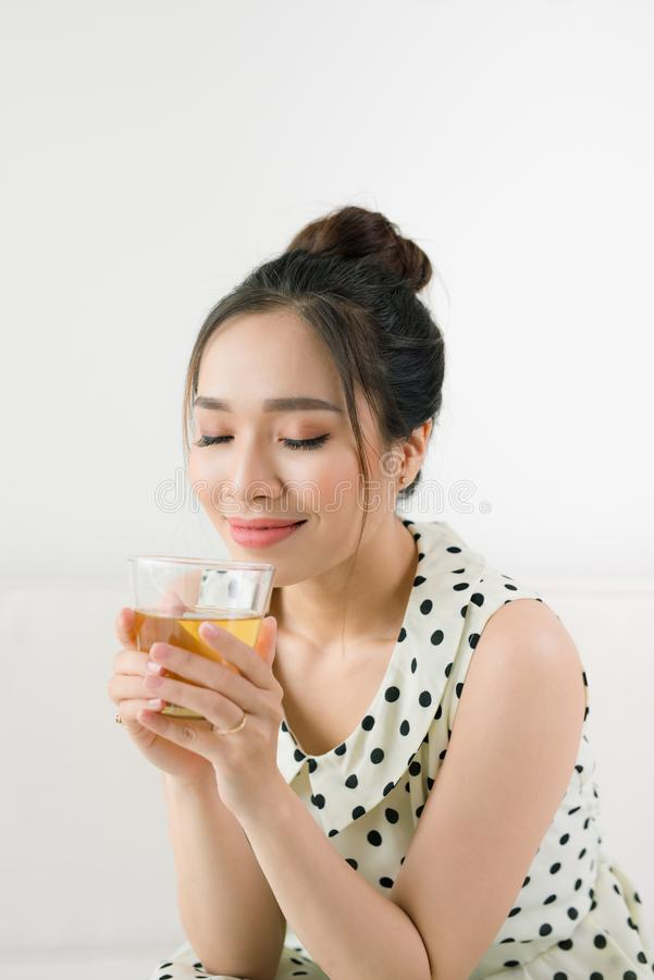 Young beautiful asian woman enjoying a cup of tea while sitting stock photos