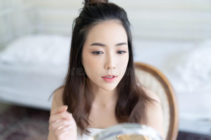 Young beautiful Asian woman with fresh Healthy Skin  looking at herself in mirror.Natural Makeup Touching Face. Cosmetic Concept stock photography