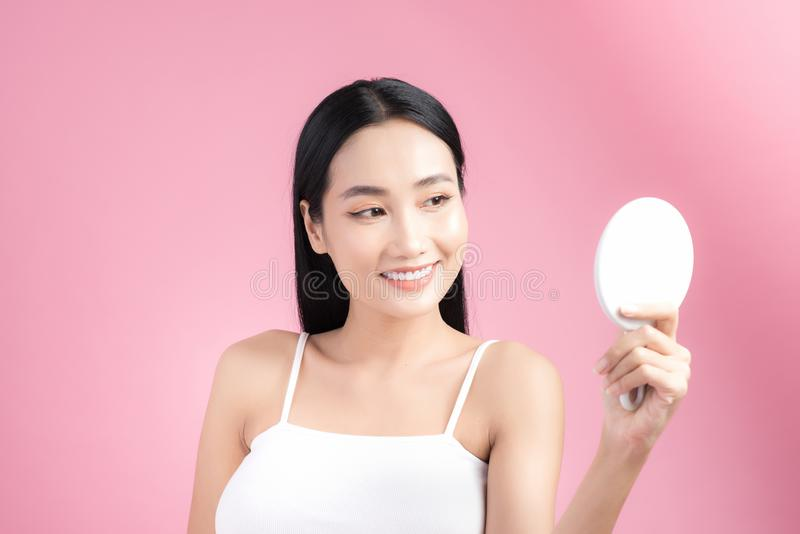 Young beautiful Asian woman looking at mirror over pink background.  stock photo