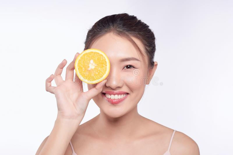 Young and beautiful asian woman posing with a slice of orange on white background.  royalty free stock images
