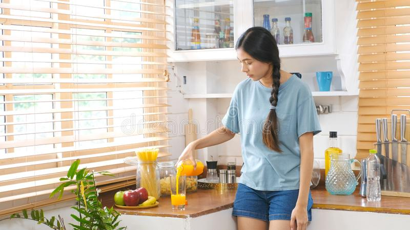 Young beautiful asian woman pouring orange juice on glass while standing in kitchen background, Asian girl drinking orange juice royalty free stock photos
