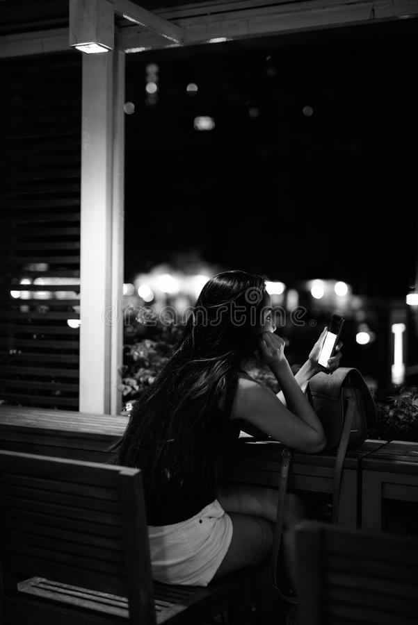 Young beautiful Asian woman relaxing at the coffee shop at night royalty free stock photography