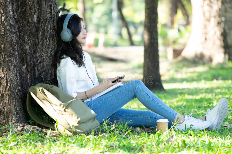 Young beautiful Asian woman relaxing and listening to music using headphones on grass in park. Lifestyle and Relax Concept. stock image