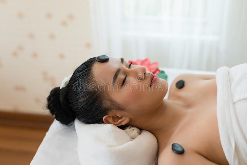 Young beautiful Asian woman relaxing in the Spa Stone Massage. B royalty free stock images