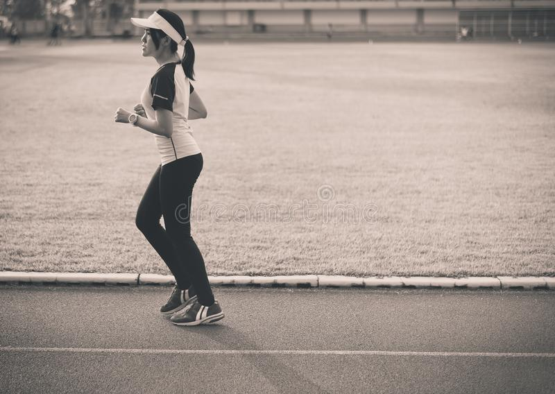 Young beautiful asian woman runner running on track during sunset,Black and white toned stock image