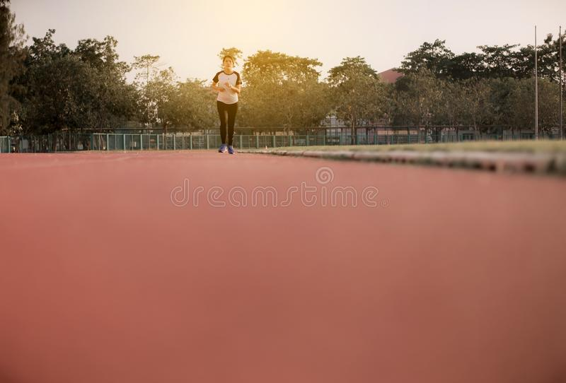Young beautiful asian woman runner running on track during sunset royalty free stock photo