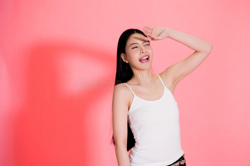Young beautiful Asian woman scared of sunshine isolated over pin royalty free stock image